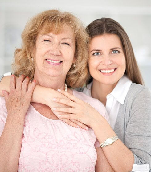 Smiling mother and daughter in dental chair