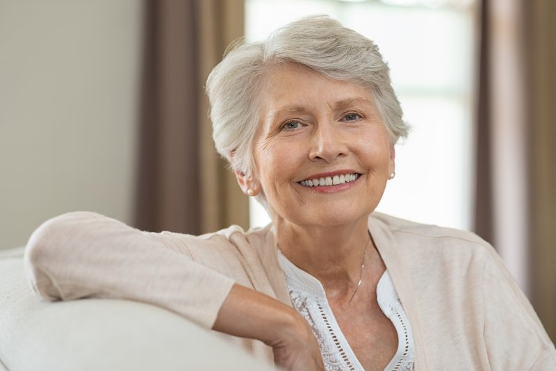 an older woman seated on a couch and smiling after receiving her dental implants
