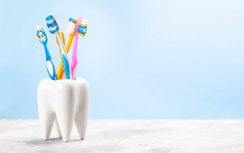 five toothbrushes sitting inside a toothbrush holder that looks like a tooth